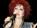 Singer Cyndi Lauper performs for delayed passengers at a Buenos Aires airport.