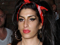 Amy Winehouse is sticking by her boyfriend Reg Traviss after a stripper claims to have been with him.