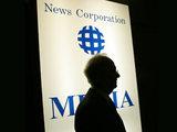 Rupert Murdoch in front of a News Corporation logo