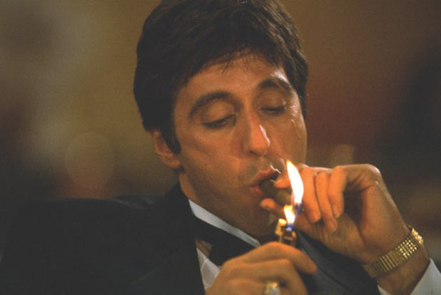 Tony Montana lights a cigar