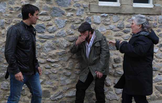 Cain Dingle (Jeff Hordley) punches Zak Dingle (Steve Halliwell) while Lisa Dingle (Jane Cox) watches on
