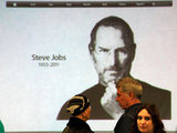 An image of Steve Jobs is shown on a screen at the Apple Store in Santa Monica following the news of his death