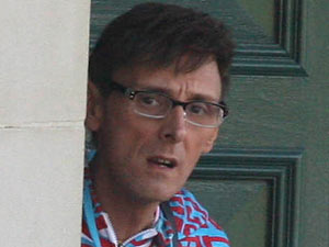 Johnny Robinson lurks from behind a corner in the garden of the 2011 X Factor contestant house