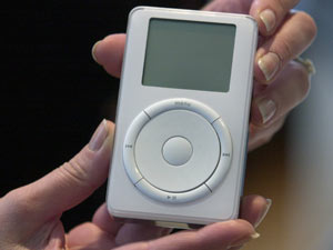 Apple's new music player, the first ever iPod is held on display after its introduction by Steve Jobs during a news conference in 2001