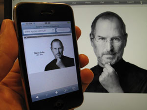 An iPhone and desktop show the memorial to Steve Jobs on the Apple website
