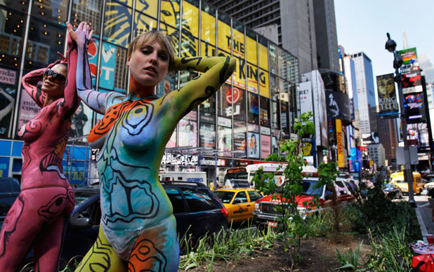Body painted models pose for photographs in Times Square as part of an Andy Golub art exhibit