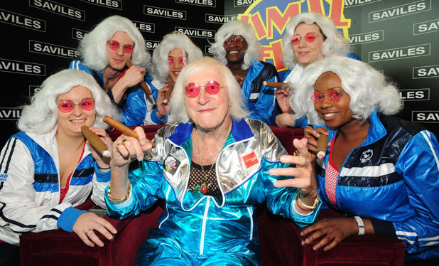 Sir Jimmy Savile with staff from the Royal Armouries in Leeds in 2009