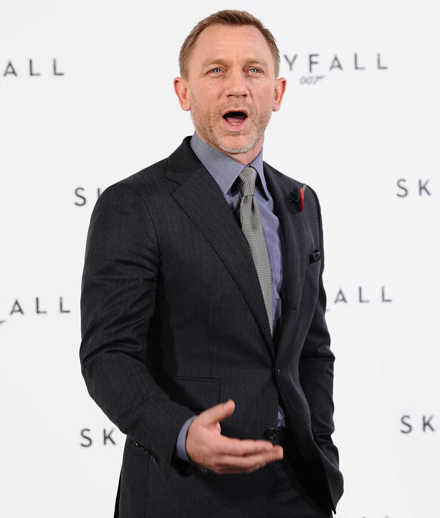 Daniel Craig shouts to the photographers