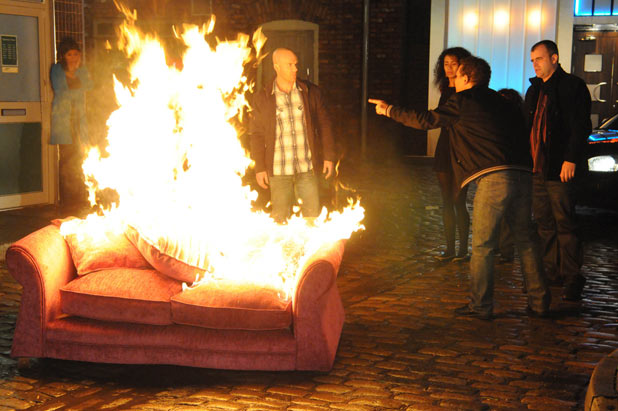 Lloyd drags a sofa onto the street and torches it