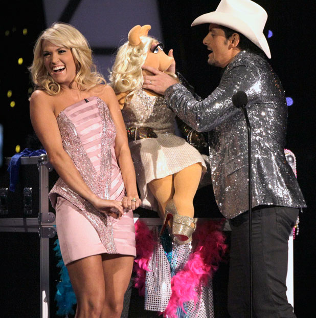 Hosts Carrie Underwood and Brad Paisley joke around with Miss Piggy from The Muppets.