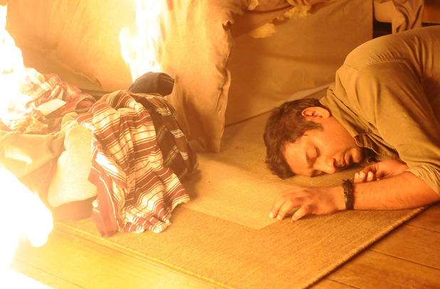 Masood lies unconscious as the fire spreads