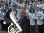 Neighbours actor Ian Smith (Harold Bishop) plays the signature theme tune with a big brass band at London's Trafalgar Square.