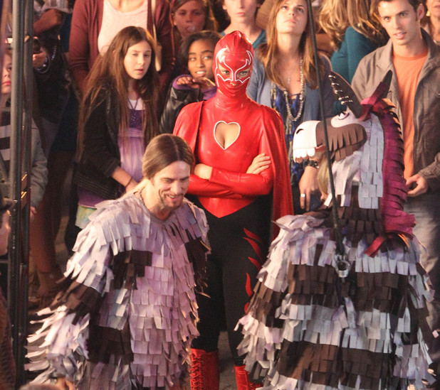Olivia Wilde in a superhero costume and Jim Carrey as a Zebra pinata