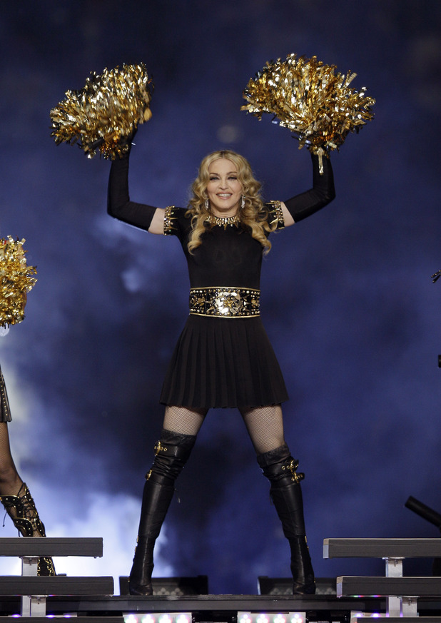 Madonna wields gold pompoms