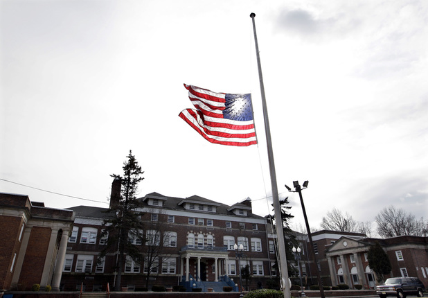 An American flag flies at half-staff in front of The Whitney E. Houston Academy of Creative and Performing Arts