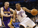 Oklahoma City Thunder guard Russell Westbrook (0) drives around Los Angeles Lakers guard Steve Blake, left, in the third quarter of an NBA basketball game in Oklahoma City,