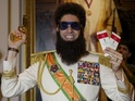 The actor poses as The Dictator with tickets to the ceremony.