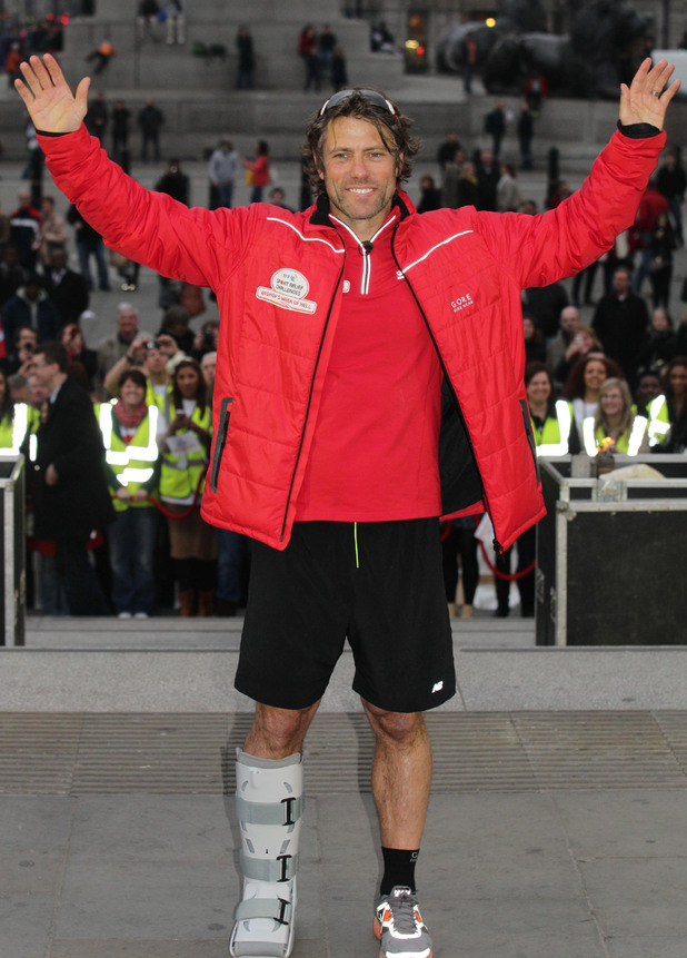 Comedian John Bishop celebrates after completing his 290 mile triathlon from Paris to Trafalgar Square in central London