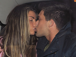 Katie Price and boyfriend Leandro Penna hug and kiss in the back of a taxi.