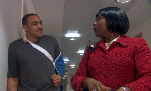 Mrs Tembe (Lorna Laidlaw) is threatened by burglar Curtis (Ike Hamilton)