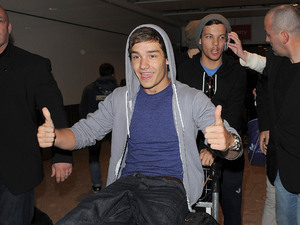 Liam Payne and Louis Tomlinson One Direction arrive at Heathrow Airport on alate night flight from Sweden. Despite it being almost midnight, they were swamped by around 70 female fans as they made their way to their car. London
