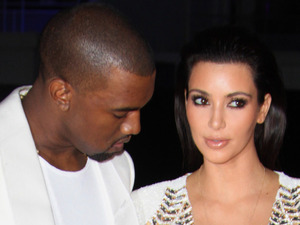 Kanye West seems a little preoccupied with something whilst being photographed with Kim Kardashian at the Cruel Summer premiere at the 65th International Cannes Film Festival