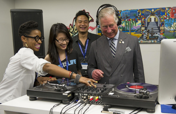 Prince Charles learns how to scratch and fade with a turntable during a tour of an employment skills workshop in Toronto, Canada