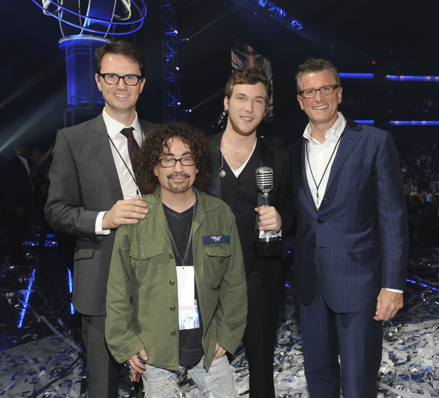American Idol winner Phillip Phillips is presented with his trophy. He's joined by (L-R) Peter Rice, Chairman, Entertainment Fox Networks Group, Mike Darnell President Alternative Programming Fox Broadcasting and Kevin Reilly, President, Entertainment, FOX Broadcasting Co.