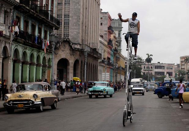 Felix Girola waves to people as he takes his self-made bicycle for a spin through downtown Havana, Cuba