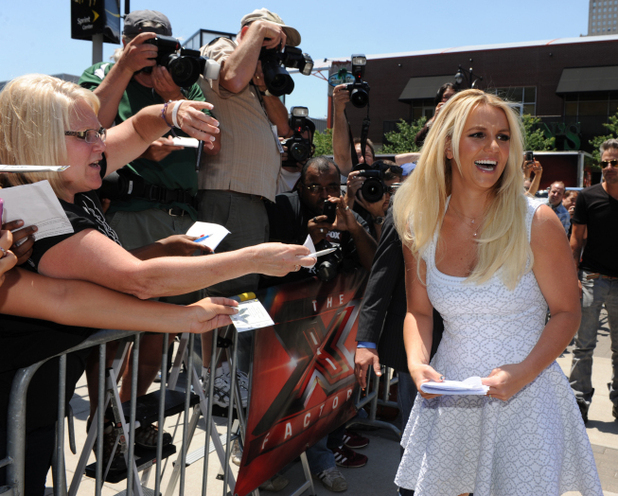 Britney Spears signs autographs for waiting fans.