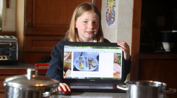 9-year-old Martha Payne with a laptop showing her blog 'NeverSeconds'