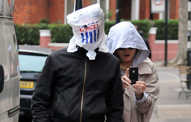 Matt Bellamy and Kate Hudson walking in North London. Bellamy covered his head with a Tesco bag, looking out through a single eye hole London, England