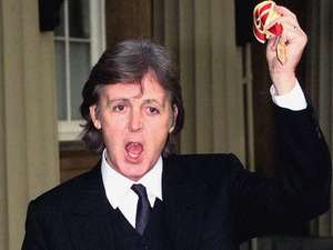 Sir Paul McCartney shows off his medal after receiving his knighthood 