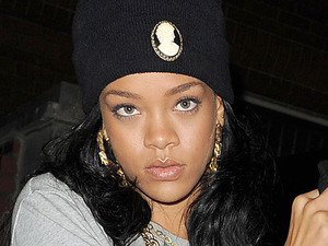 Rihanna arriving at a recording studio late at night, wearing a t-shirt featuring a gun logo and a cussword. London