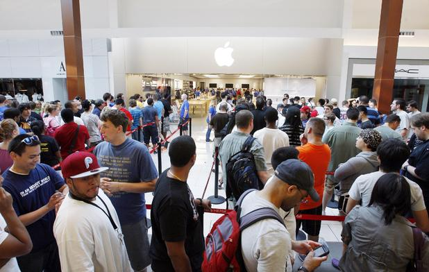 A large crowd stands in line outside the Apple Store