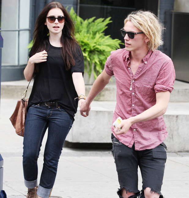 Lily Collins and her 'The Mortal Instruments' co star Jamie Cambell Bower hold hands as they leave their residence to grab Starbucks before heading out to an outdoor patio. Toronto, Canada