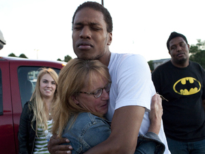Judy Goos, second from left, hugs her daughters friend, Isaiah Bow, 20, while eye witnesses Emma Goos, 19, left, and Terrell Wallin, 20, right, gather outside Gateway High School where witness were brought for questioning after the shooting at the premiere of the new Batman film in Colorado