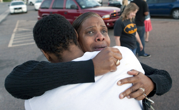 Shamecca Davis hugs her son Isaiah Bow, who was an eye witness to the shooting, outside Gateway High School where witness were brought for questioning after the shooting at the premiere of the new Batman film in Colorado