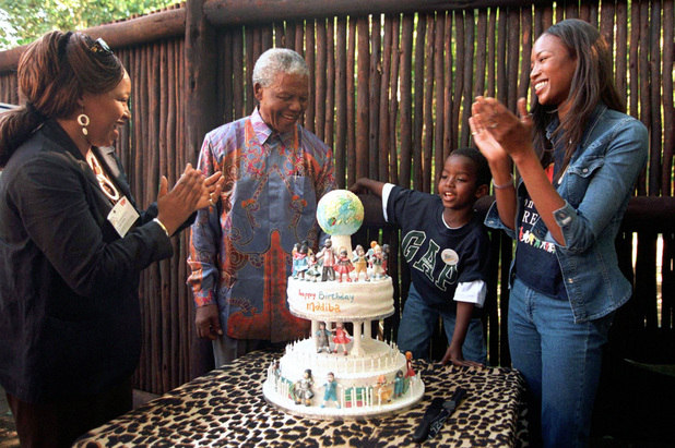 Nelson Mandela is applauded by Naomi Campbell and his family at a special birthday party in 1998 when he turned 80 years old
