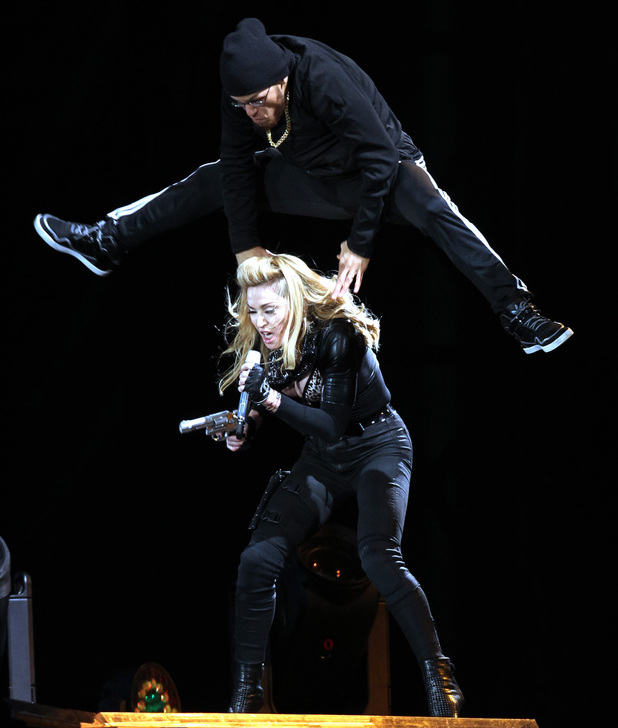 A performer jumps over Madonna