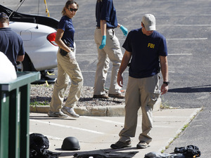 Investigators look over evidence on ground outside the back door of the Century 16 movie theater east of the Aurora Mall in Aurora, Colo. on Friday, July 20, 2012 following the shootings during a Batman screening