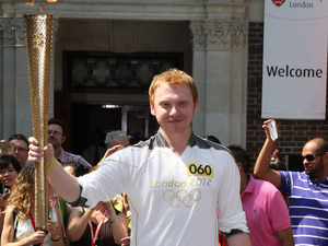 Actor Rupert Grint carries the Olympic Torch during the relay as it visits Middlesex University in London