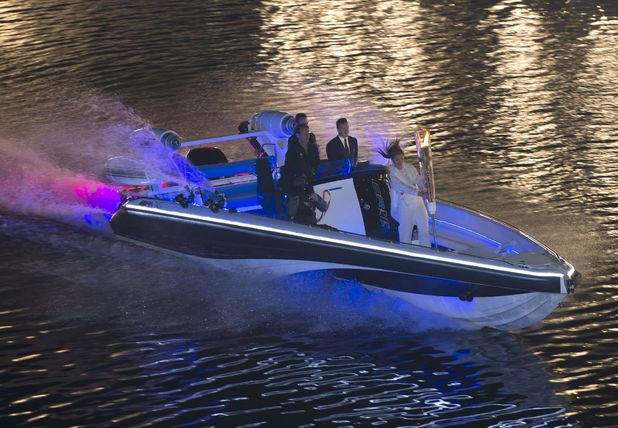 David Beckham arrives by boat with the Olympic Torch.