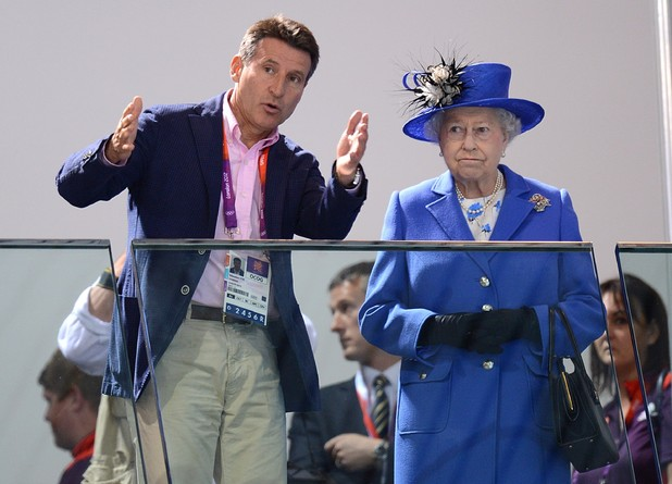 Lord Sebastian Coe speaks to the Queen as they watch the morning session of the Swimming on Day 1 of the Olympics.