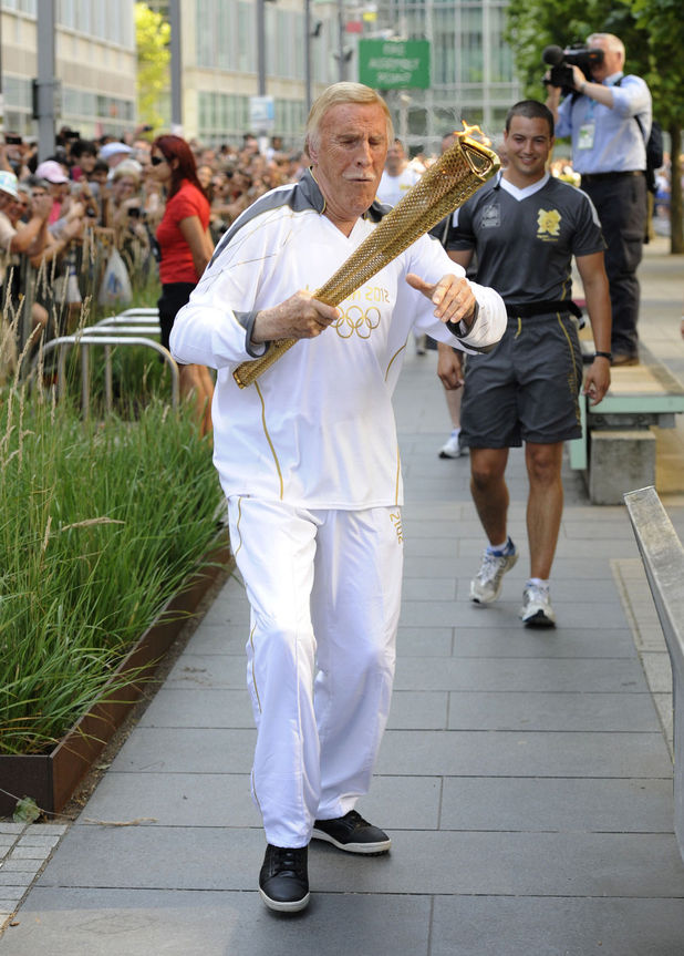 Bruce Forsyth carries the Olympic Flame on the Torch Relay leg through Kensington and Chelsea