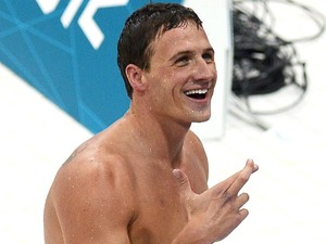 USA swimmer Ryan Lochte smiles toward fans and has his fingers crossed after he claimed the gold medal in the Men's 400m Individual Medley
