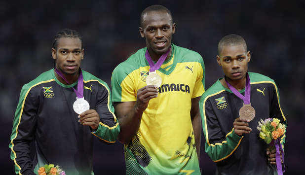 Jamaica's gold medal winner Usain Bolt is flanked by his teammates silver medal winner Yohan Blake, left, and bronze medalist Warren Weir during the ceremony for the men's 200-meter final during the athletics in the Olympic Stadium (August 9)