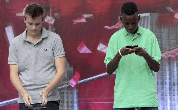 Austin Wierschke, left, places his phone on a podium after finishing texting ahead during the final round of the 2012 LG U.S. National Texting Championship