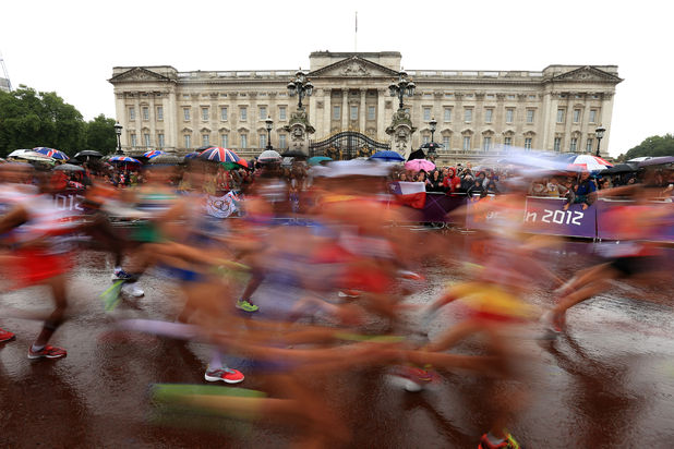 Runners in the women's marathon run past Buckingham Palace, London
