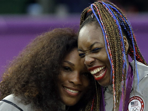 Serena Williams, left, and Venus Williams of the United States laugh together on the podium after receiving their gold medals in women's doubles at the All England Lawn Tennis Club in Wimbledon, London at the 2012 Summer